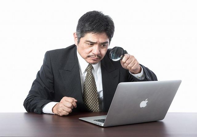 パソコンを虫眼鏡で見る男